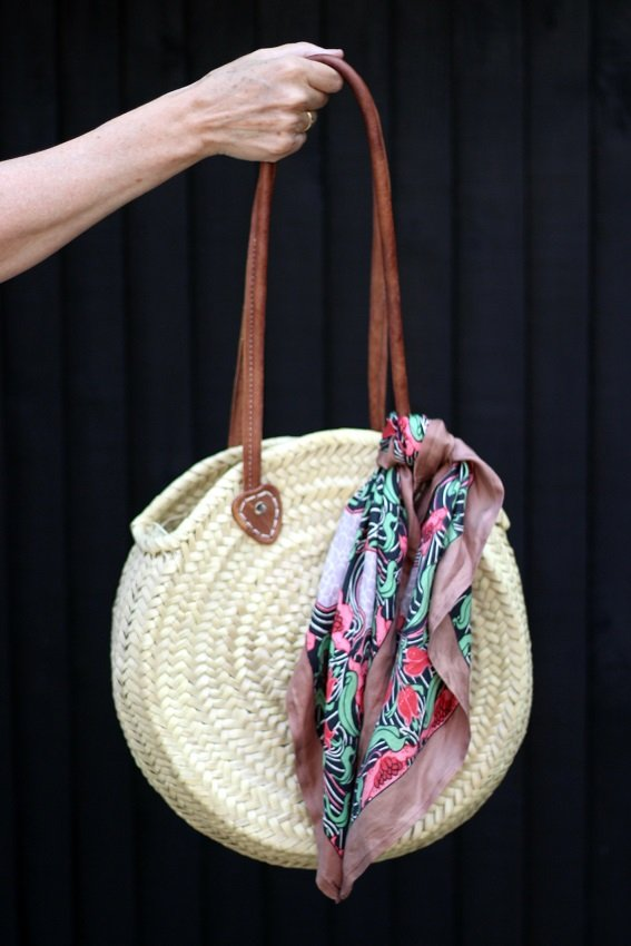liberty print scarf tied to a straw bag
