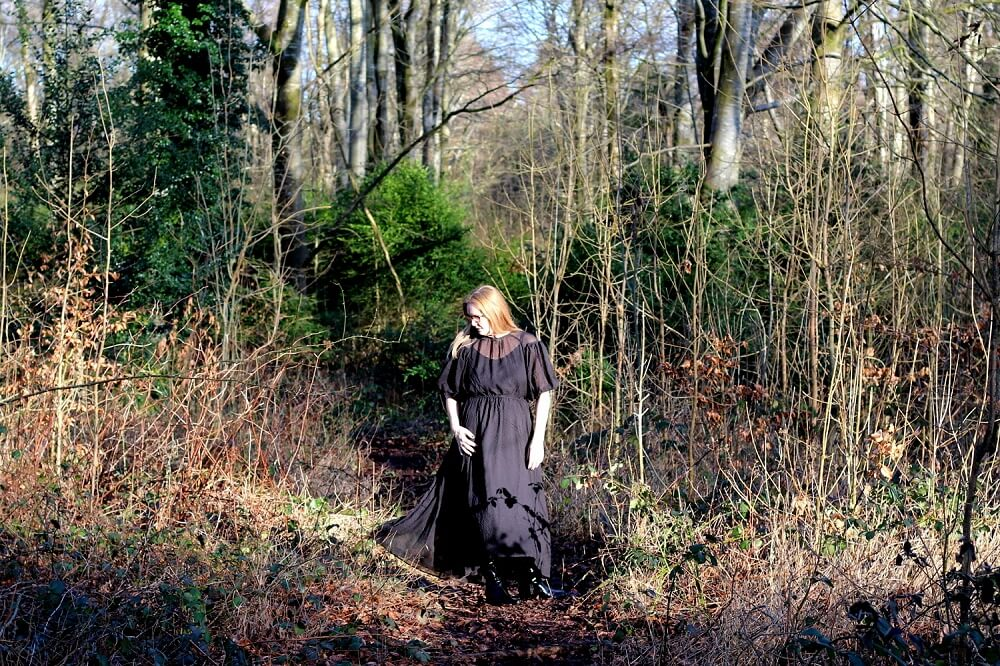 Lazy daisy jones wearing a black dress from H&M walking in a forest.